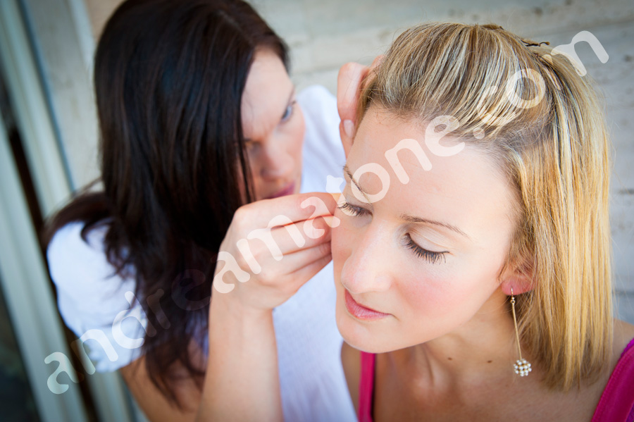 Bridesmaid helping putting an earring on