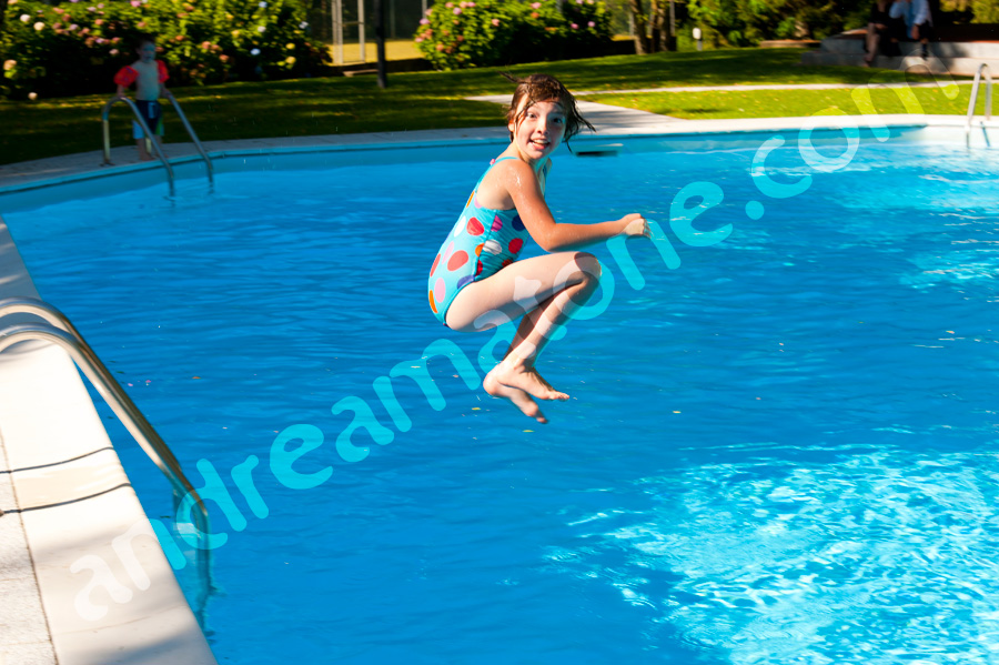 Little girl jumpin in the swimming pool