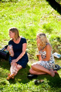 Guests relaxing in a green field after wedding