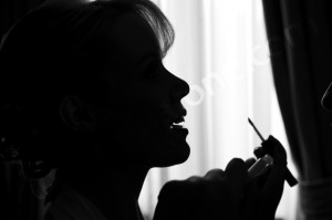 Bride in silhouette during make up session