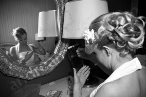 Bride putting necklace on in black and white