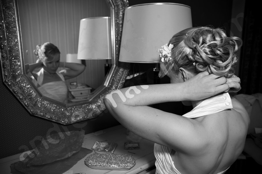 Bride getting ready in front of the mirror in a Hotel