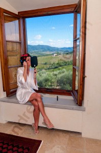 The bride is getting ready by the window with Tuscan view