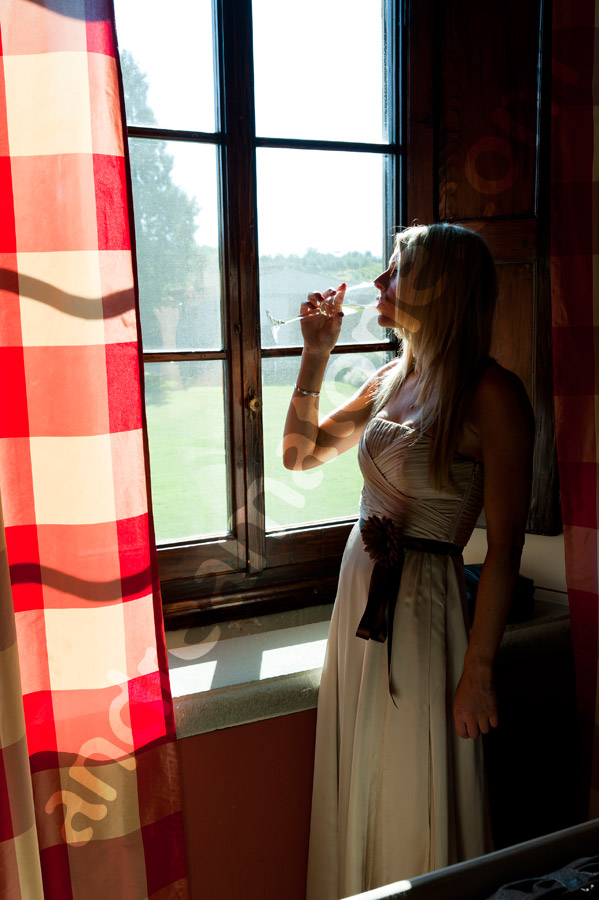 Bridesmaid having a drink and looking at the Tuscan countryside in Italy