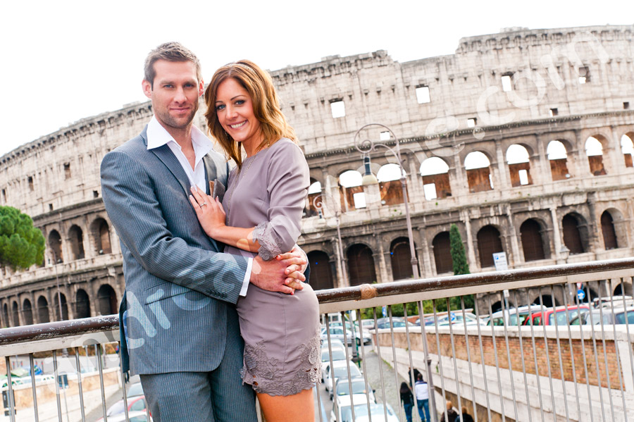 Man and woman on the bridge before the Coliseum in Italy.