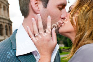 Couple kissing during engagement session with ring close up