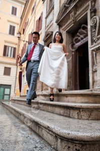 Newlyweds stepping downstairs from a Church in Rome