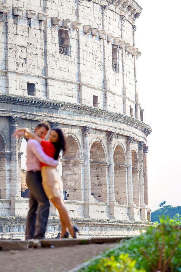 Out of focus photography in front of the Roman Colosseum with a beautiful couple posing