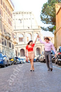 Couple in romantic dance poses in Rome walking away from the Colosseum