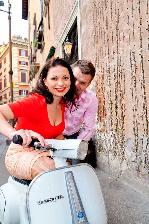 Couple posing for a picture on a white vespa