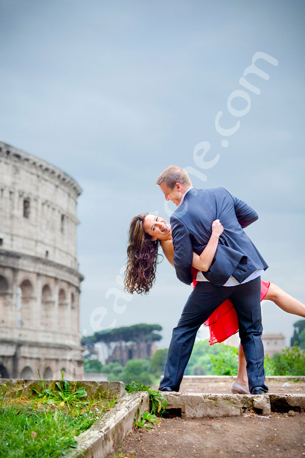 Engagement photography by the Coliseum under uncertain blue sky.