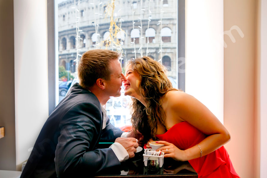Kissing inside a cafe shop bar in center of the city with the view of the Colosseum in the back. Rainy Engagement Photos in Rome.