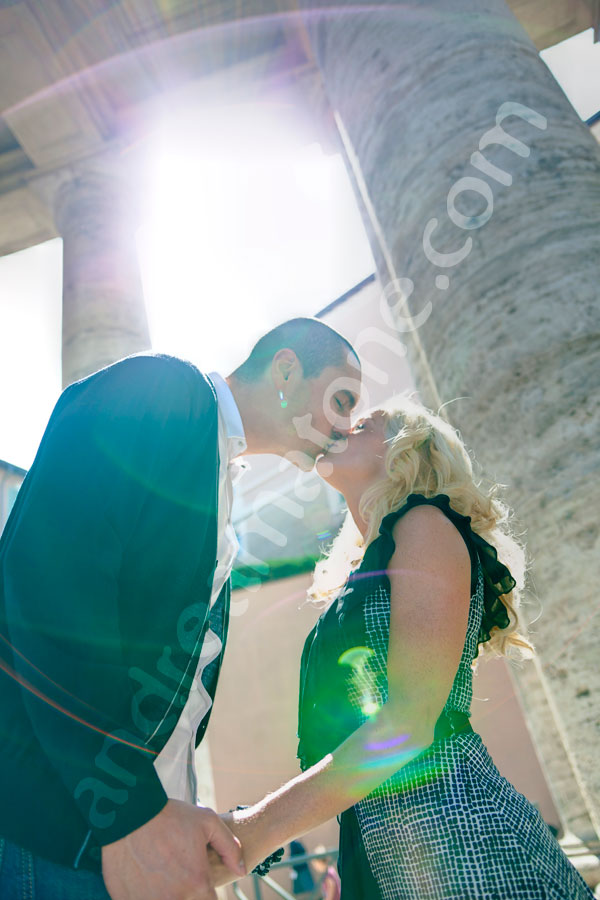 Couple kissing under ancient columns in Saint Peter's square colonnade