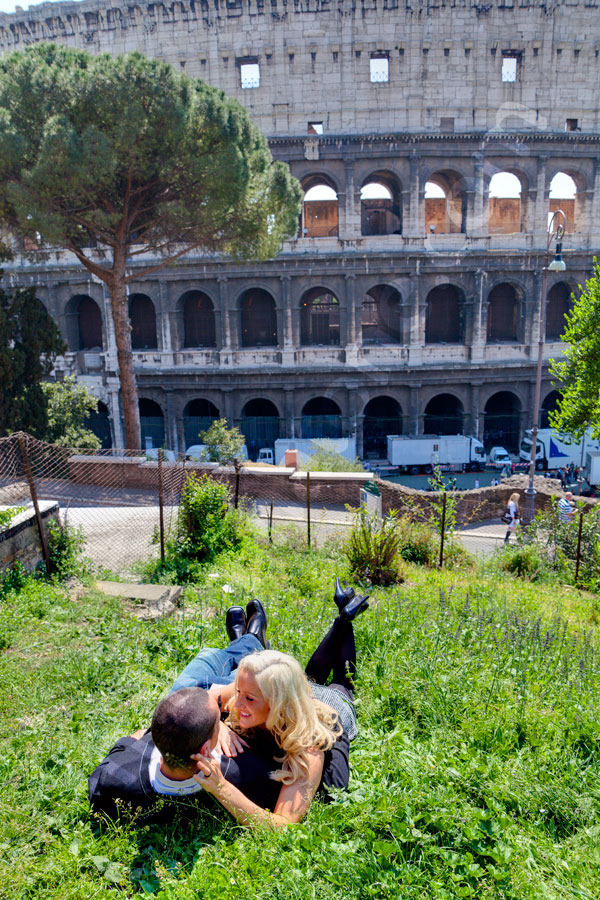 Laying down in green grass by the Roman Colosseum