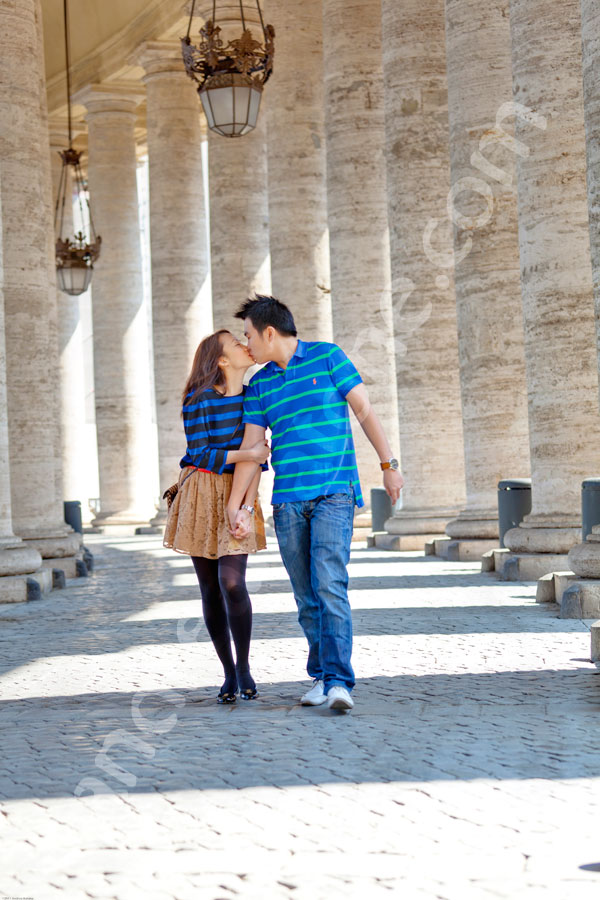 In love underneath the Colonnade of Saint Peter's square in the Vatican city.