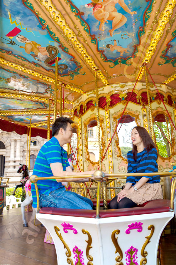 Wedding engagement couple having fun on a carousel