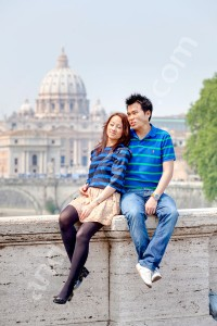 Engaged couple sitting down in front of Saint Peter's square with the Dome in the distance