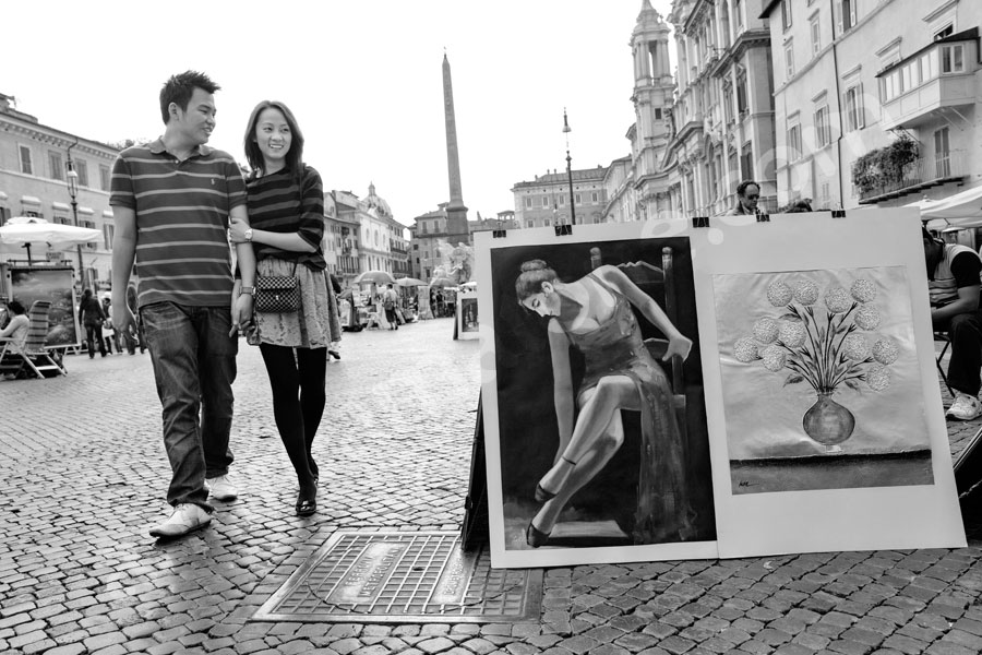 Black and white picture taken in Piazza Navona as they walk by.