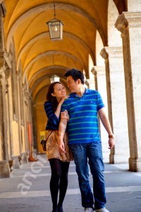 Couple holding on to each other walking underneath the portico in Church San Ivo alla Sapienza Rome Italy