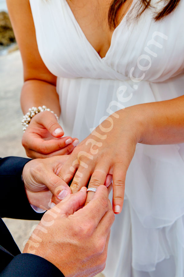 Putting the ring on a bride's hand during a private wedding ceremony