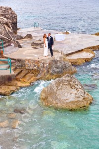 Wedding couple photographed by a photographer at a distance by the sea