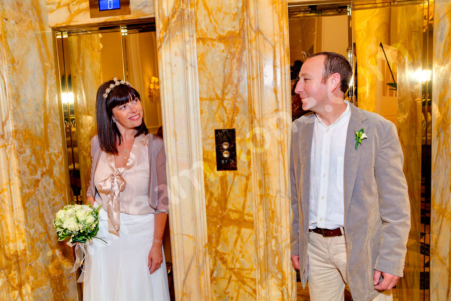 Bride and groom standing next to each other by a hotel elevator
