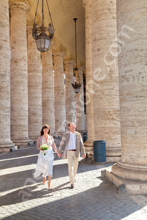 Walking under the colonnade in Saint peter's square in the Vatican.