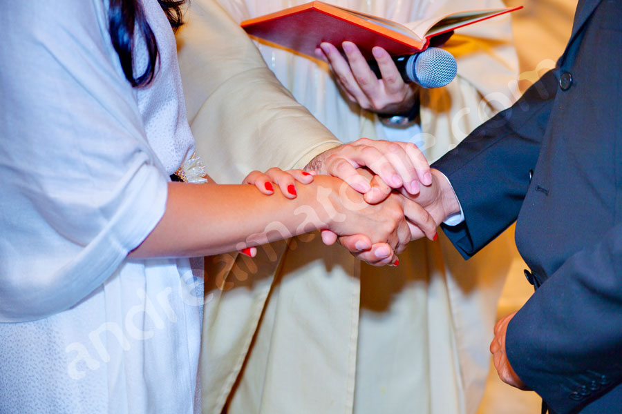 newlyweds joining hands in a symbol of marriage