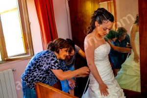 The bride wearing the wedding dress during the preparation