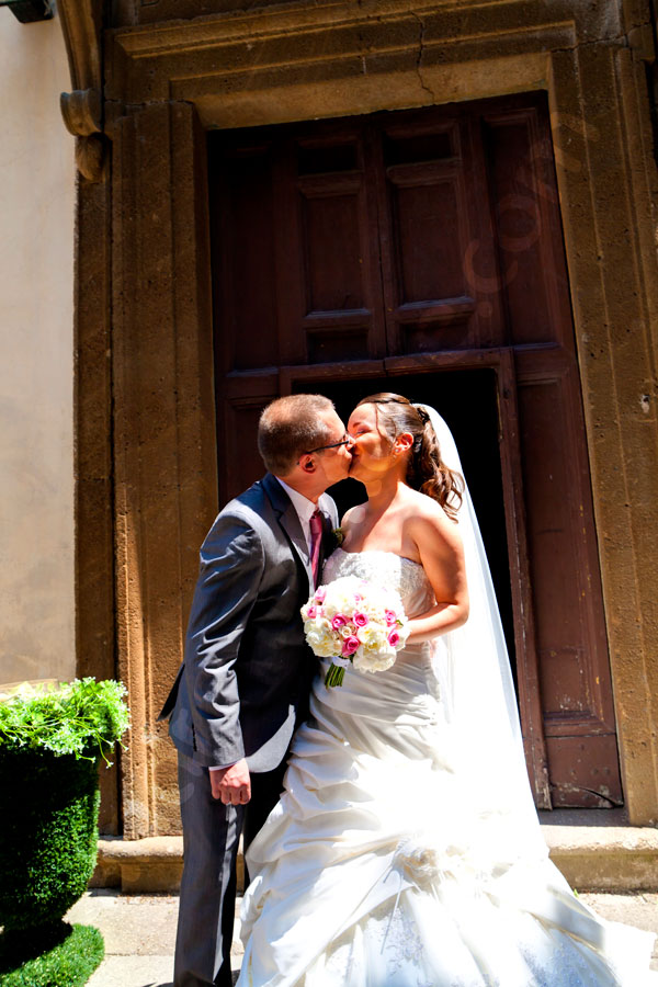 Newlyweds kissing each other under the sun