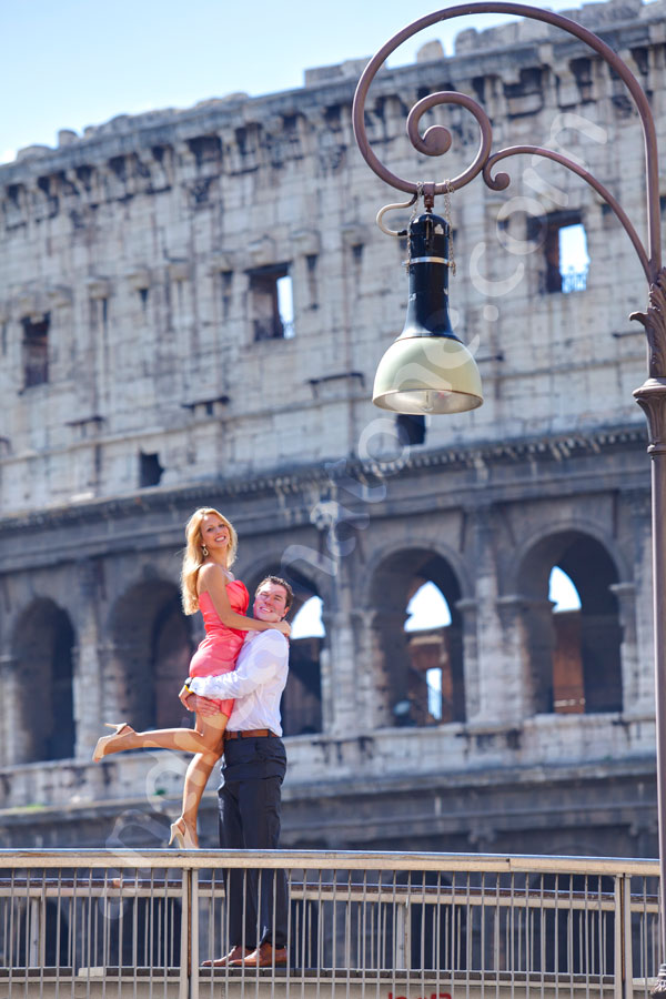 Man holding woman up high before the Roman Colosseum