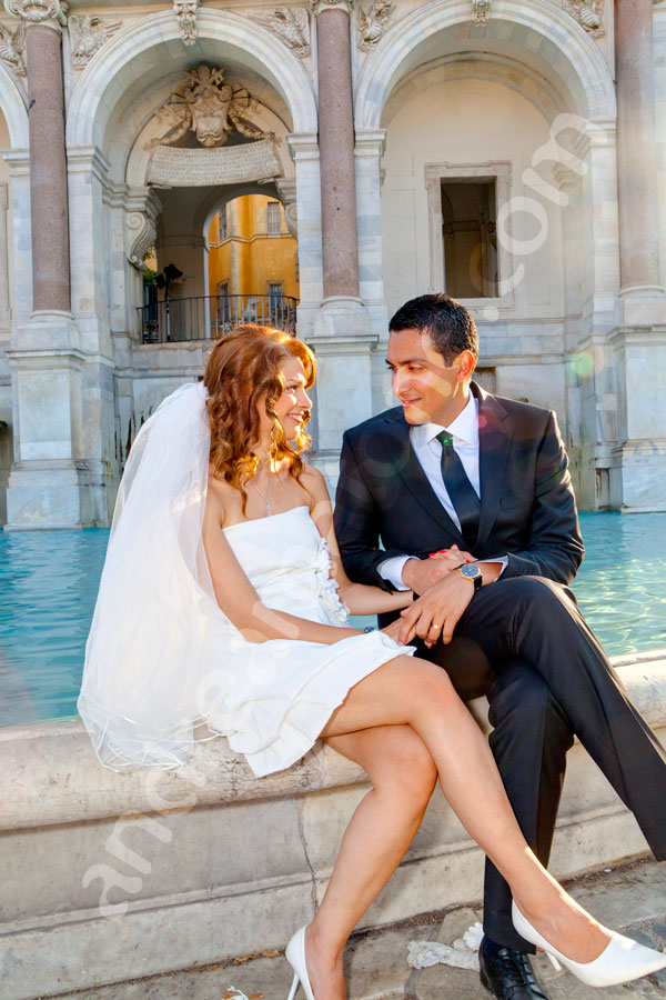 The bride and groom sitting on the edge of Fontana Fontanone del Gianicolo