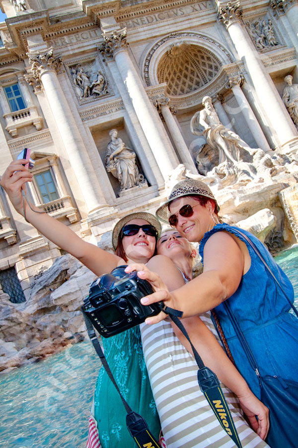 Tourists photographers taking a funny picture of themselves in Piazza Fontana di Trevi. Vacation pictures.
