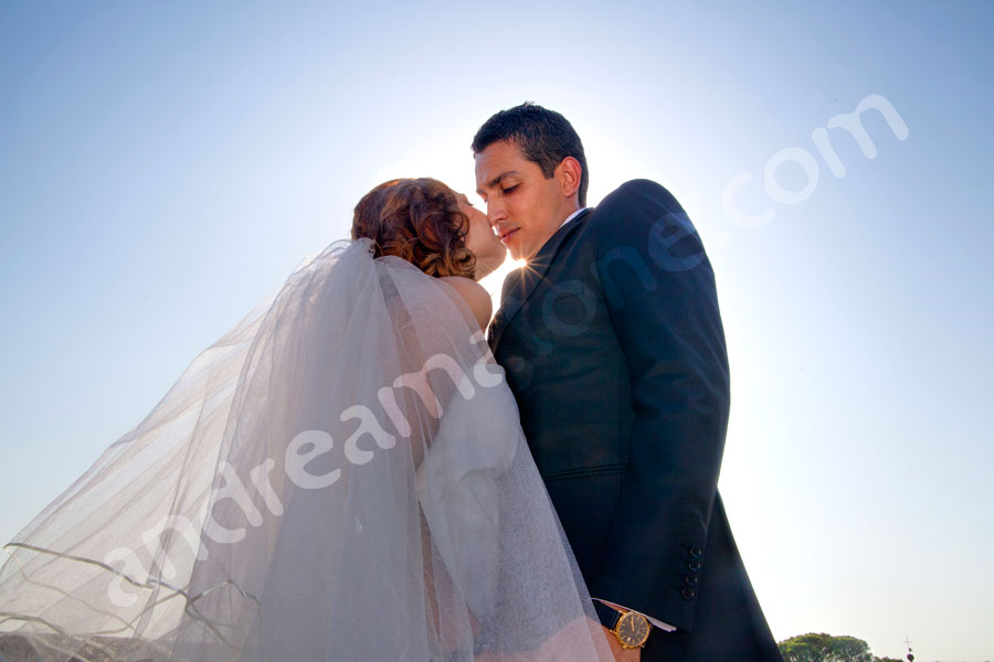 Bride and groom kissing in blue sky