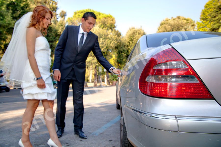 Groom opening the car door for the bride