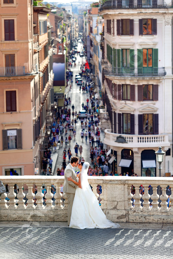 Kissing after the wedding in Piazza di Spagna with the view of Via Condotti in the far distance