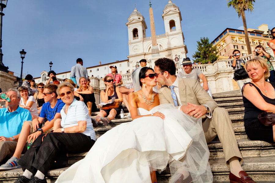 Best Wedding Photographers in Rome Italy. The bride and groom romantically kissing among tourists on the Spanish steps.