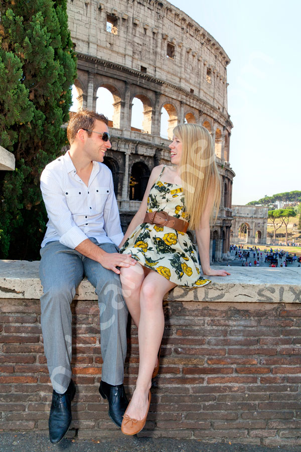 Couple in honeymoon sitting down in front of the Colosseum and having fun talking