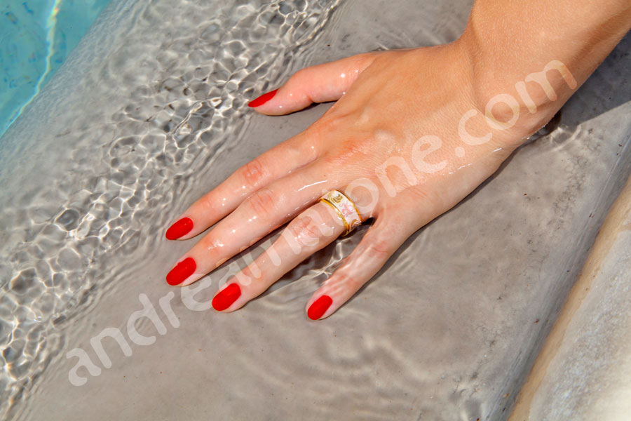 Wedding ring on a woman's finger immersed in the water of the Gianicolo Fountain Fontanone