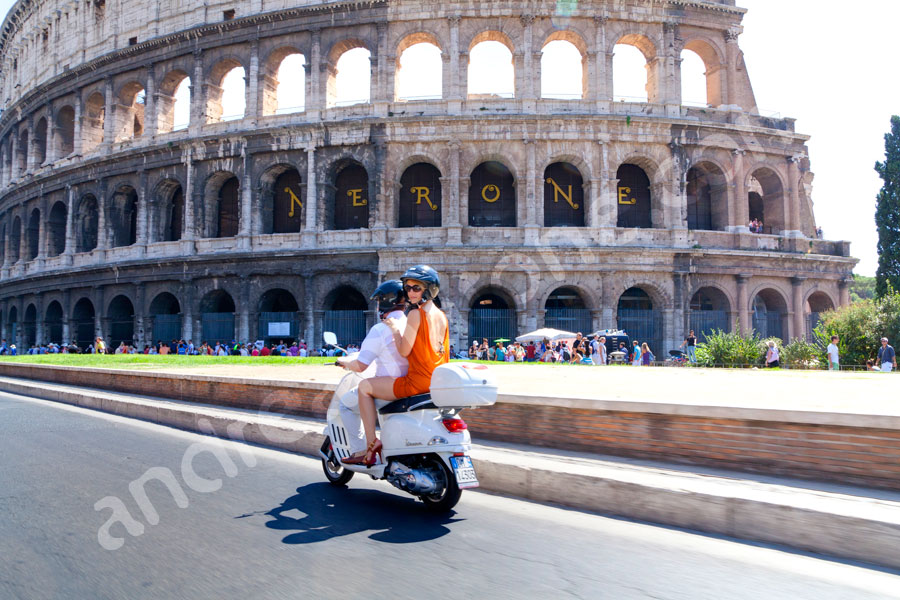 Couple riding a vespa through the city of Rome with the Coliseum in the background. Vacation photography.
