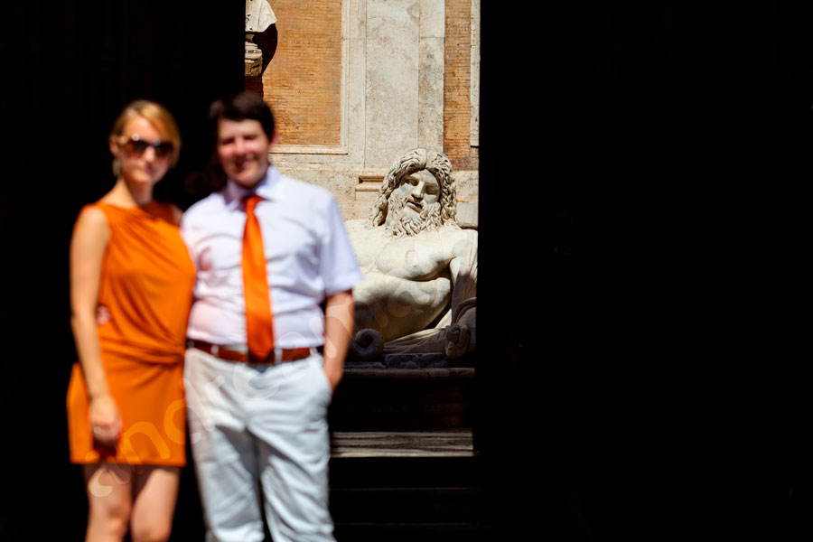 Couple standing in front of a Roman statue in Piazza del Campidoglio