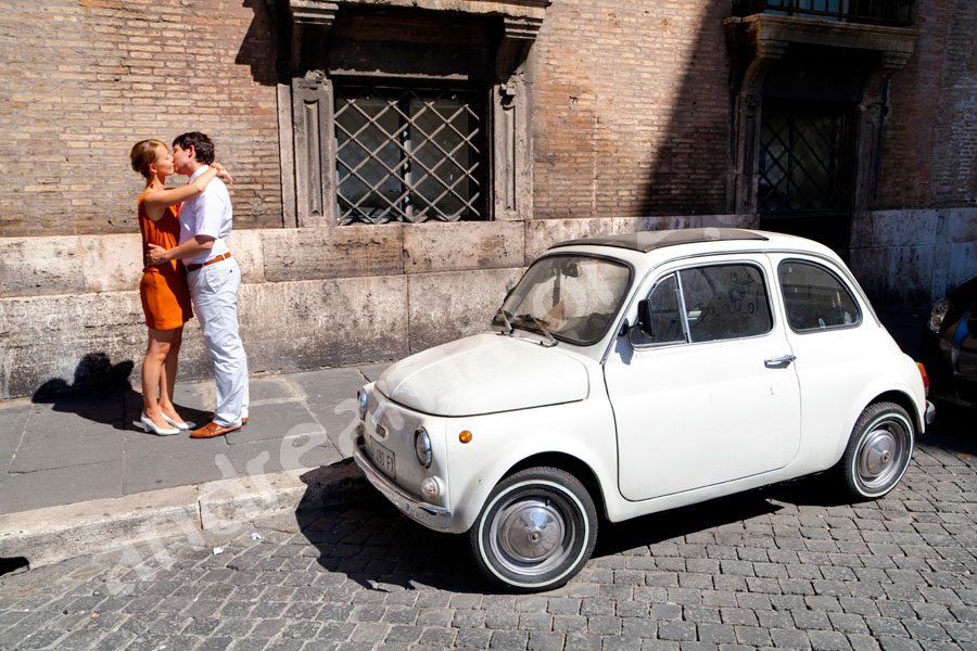 Kissing by an old vintage FIAT 500 cinquecento in the streets