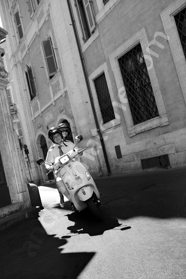 Riding a vespa scooter through the roman alleyways like in Vacanze Romane movie