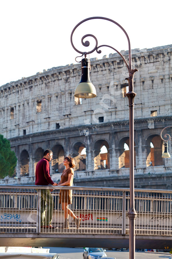 Couple hanging out on a bridge before the Colosseum