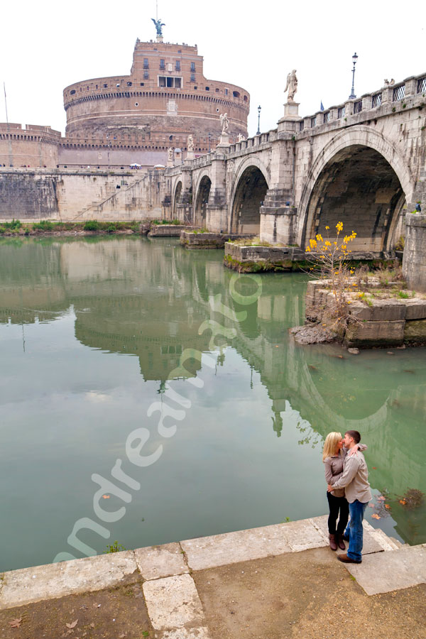 Couple romantically kissing by the Tiber river banks.