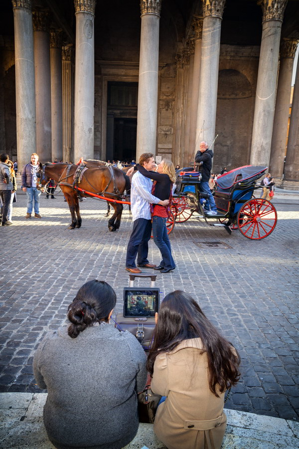 Couple romantically in love. Pantheon. While tourists watch tv waiting.