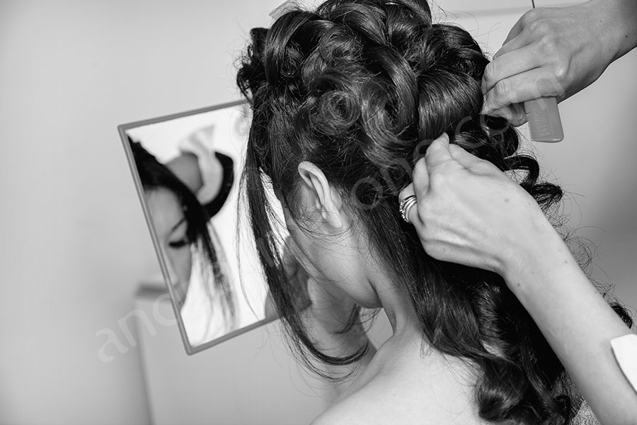 Bridal party getting hairstyle done during preparation