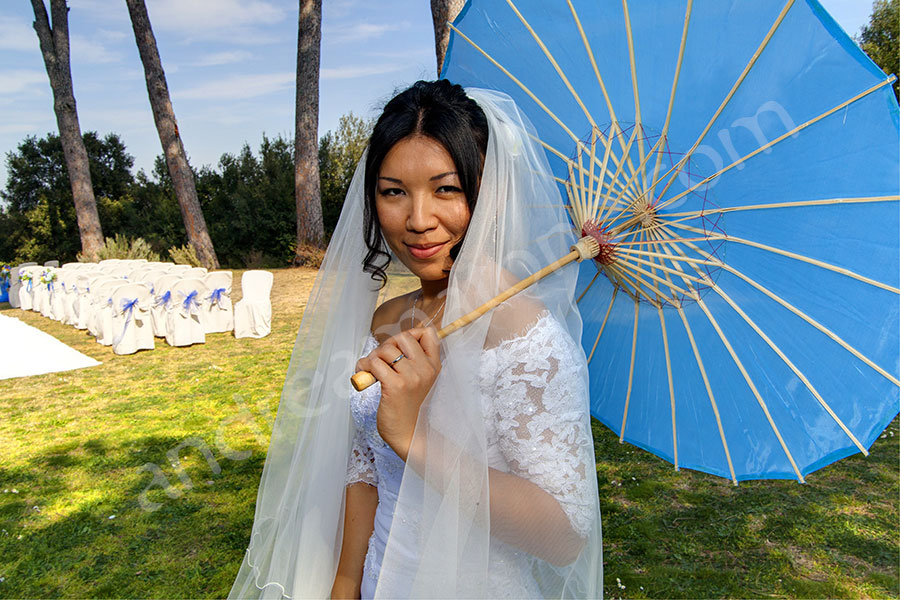 Beautiful picture of the bride holding a blue sun umbrella
