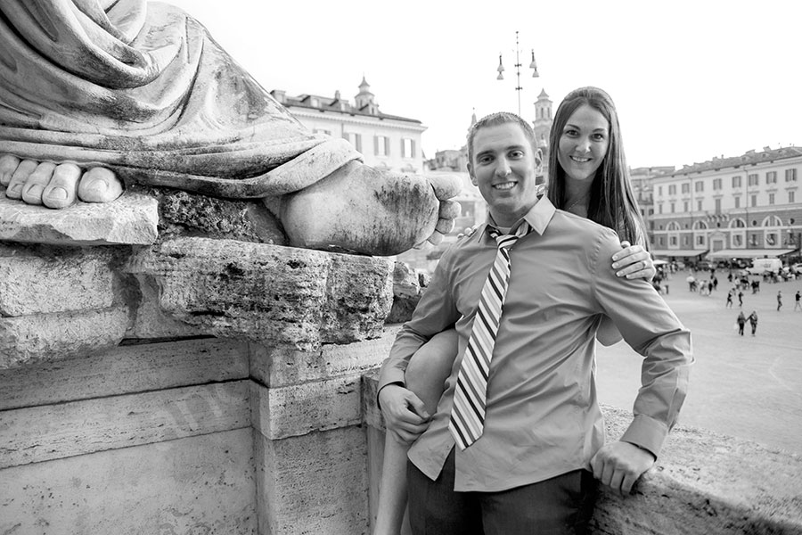 Couple engagement session by a foot statue in Piazza del Popolo.