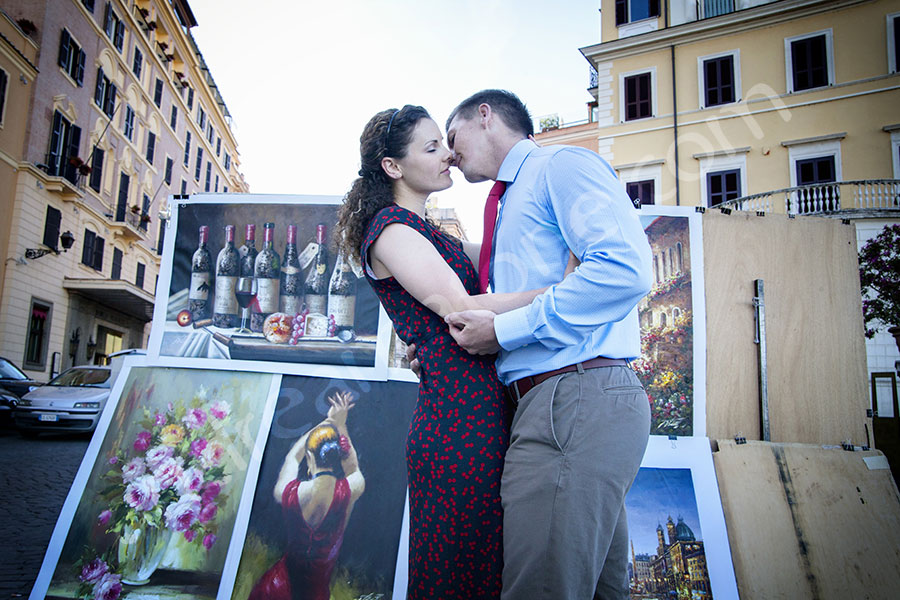 Couple kissing in love in Piazza Trnita' dei Monti by some artistic paintings.